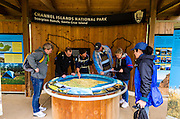 Visitors looking at interpretive display at Scorpion Ranch, Santa Cruz Island, Channel Islands National Park, California USA