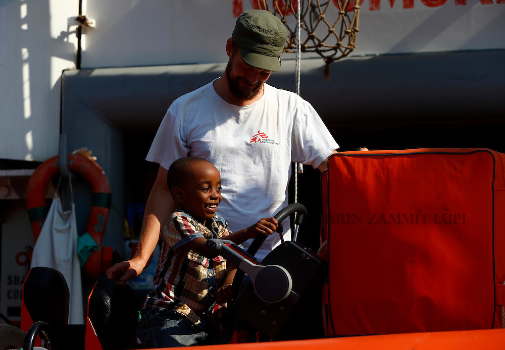 A migrant child plays on a rigid hulled inflatable boat (RHIB) under the watchful eye of an Medecins san Frontiere (MSF) team member on board the MSF rescue ship Bourbon Argos somewhere between Libya and Sicily August 8, 2015.  Some 241 mostly West African migrants on the ship are expected to arrive on the Italian island of Sicily on Sunday morning, according to MSF.<br /> REUTERS/Darrin Zammit Lupi <br /> MALTA OUT. NO COMMERCIAL OR EDITORIAL SALES IN MALTA