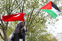 London, UK. 11th May, 2021. A demonstrator climbs a lamp post with a Palestinian and a Turkish flag as thousands of people attend an emergency protest in solidarity with the Palestinian people organised outside Downing Street by Palestine Solidarity Campaign, Friends of Al Aqsa, Stop The War Coalition and Palestinian Forum in Britain. The rally took place in protest against Israeli air raids on Gaza, the deployment of Israeli forces against worshippers at the Al-Aqsa mosque during Ramadan and attempts to forcibly displace Palestinian families from the Sheikh Jarrah neighbourhood of East Jerusalem.