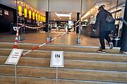 Nederland, Nijmegen, 30-4-2020 Een klant van de bibliotheek komt haar tasje met online bestelde boeken ophalen . De medewerkers zoek zelf op aangeven van genre vookeueren een aantal titels uit . De binnenstad van Nijmegen is zo goed als leeg . Mensen blijven thuis om zo min mogelijk risico te nemen ivm het corona virus . De openbare bibliotheek, bieb is dicht . Foto: Flip Franssen