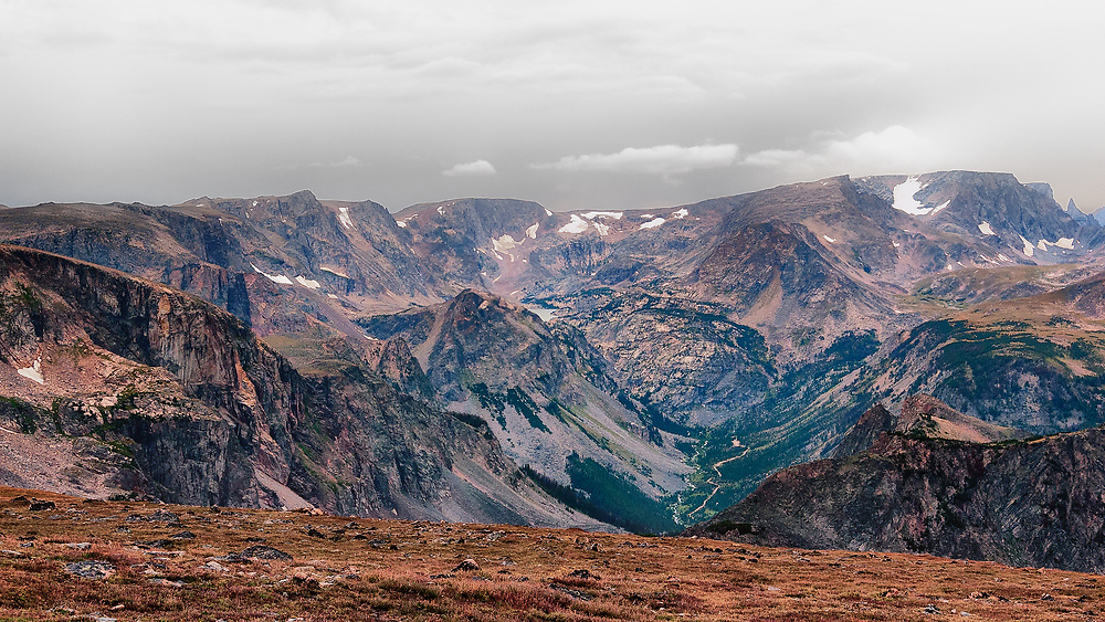 SUBJECT: Mountains IMAGE: From over 10,000 feet, cirques, small glaciers, glaciated valleys, scree slopes thin air and alpine meadows grace this tortuous terrain. The scale is deceptive. Valley floor is about 6,000 ft while the camera is over 10,000 feet. The pointed peak, top right, gave the range its name.