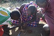 Kenya, Masai Mara, members of the Masai tribe entertain tourists by lighting a fire