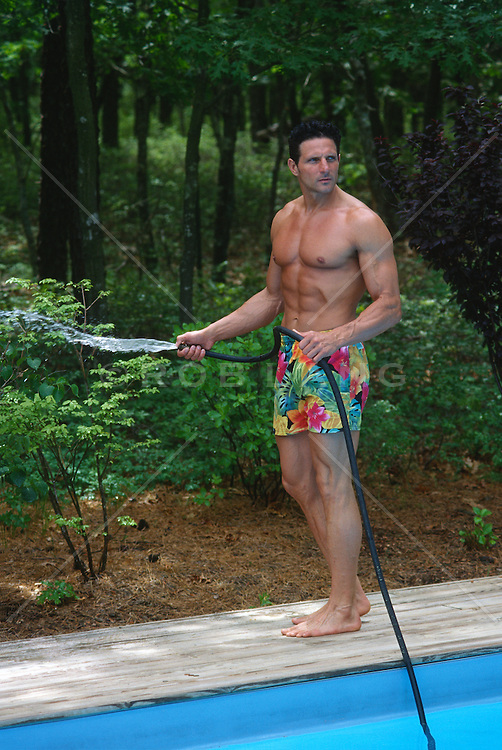Muscular man in a colorful bathing suit water plants with a garden hose