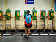 30 MAY 2017 - BANGKOK, THAILAND: A woman uses a pay phone in Hua Lamphong train station. Most of the public pay phones in Bangkok have been pulled out because people are using cell phones.      PHOTO BY JACK KURTZ