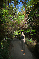 Woman visitor exploring tropical rainforest of Hapu`u Pulu or Fern Tree, Cibotium glaucum, and `Ohi`a Lehuna, Metrosideros polymorpha, Hawaii Volcanoes National Park, Kilauea, Big Island, Hawaii