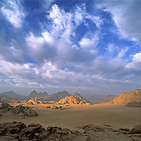 Clouds sweep over the mountains and sandy plains of Jordan's Wadi Rum, In the Arabian Desert. (The view is from Jebel (Mount) Burdah.)