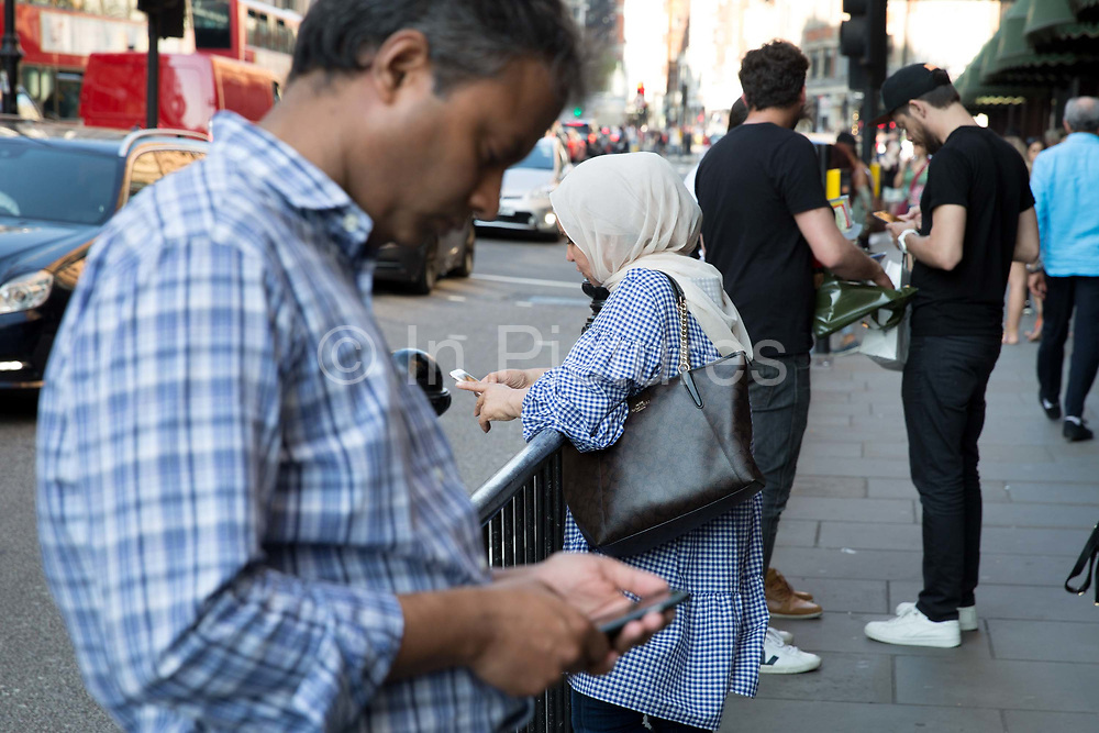 Shoppers on Brompton Road look at their mobile phones on 26th May 2017 in London, United Kingdom. From the series Our Small World, an observation of our mobile phone obsessions