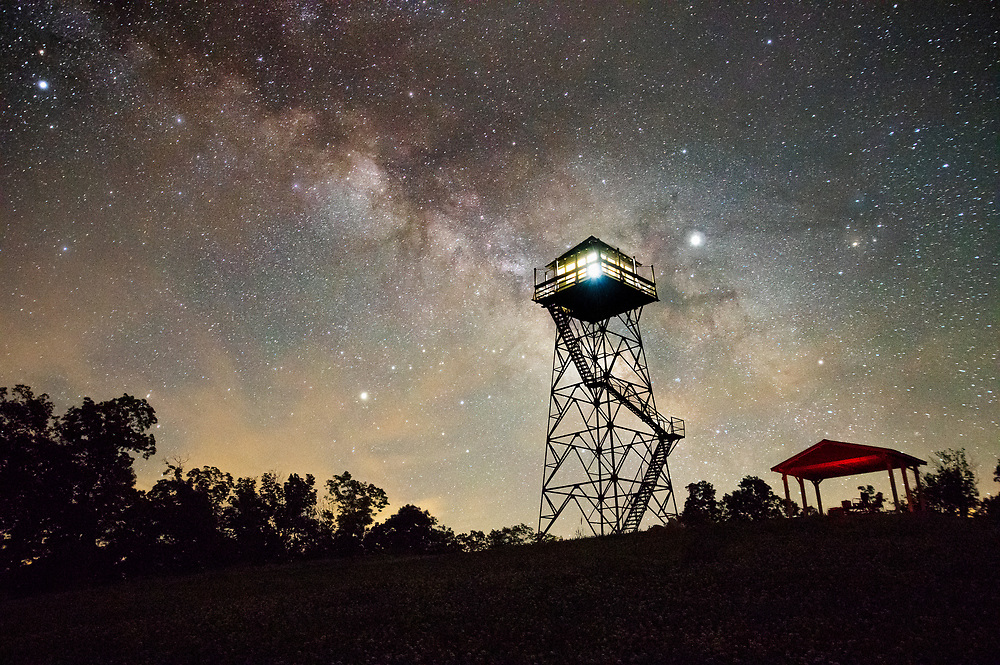 The center of the Milky Way streams behind the Thorny Mountain Fire Tower, lit up from inside, on an early summer night in Seneca State Forest of West Virginia.
