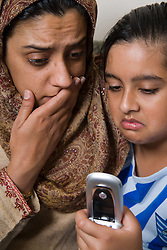 Mother and child looking worried at mobile phone,