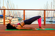 Young athletic woman in sports clothes stretching on a mat on a wooden deck in a marina