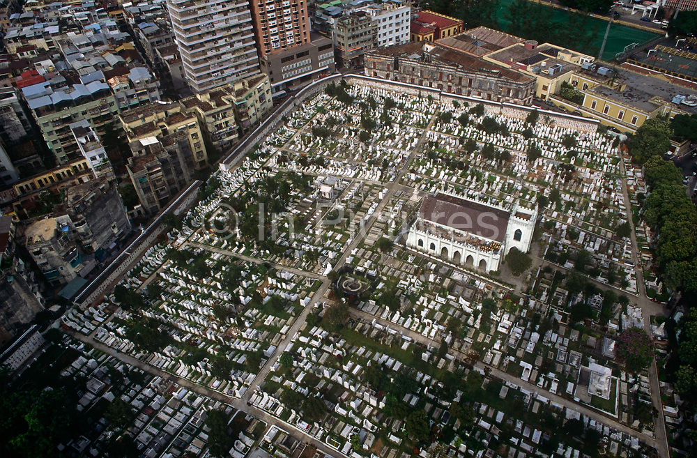 An aerial view overlooking the Cemiterio de São Miguel Arcanjo Saint Miguel Catholic Cemetery the ex-Portuguese colony of Macaus Chinese Christian cemetery of San Miguel, on 10th August 1994, in Macau, China. The cemetery is located right in the middle of Macao island, on Estrada do Cemiterio and host the graves of the old Dutch and Portuguese colonials that helped shape Macau, now one of the worlds most densely-populated city. The Macau Special Administrative Region is one of the two special administrative regions of the Peoples Republic of China PRC, along with Hong Kong. Administered by Portugal until 1999, it was the oldest European colony in China, dating back to the 16th century. The administrative power over Macau was transferred to the Peoples Republic of China PRC in 1999, 2 years after Hong Kongs own handover.