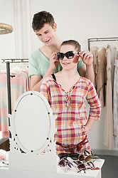 Young couple trying sunglasses and having fun at fashion store, smiling