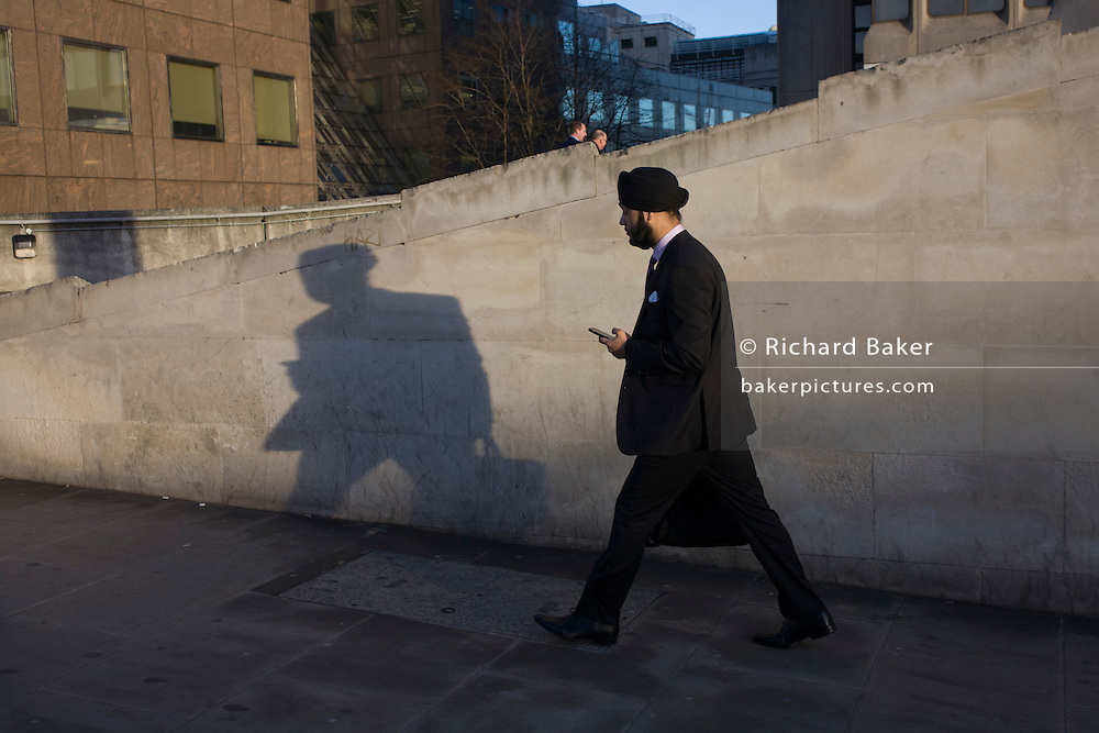 A Sikh man walks on the south side of London Bridge in Southwark, central London