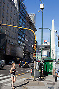 A woman walks in the street with the Obelisk in the background, Buenos Aires, Federal District, Argentina.