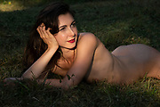 Nude woman laying in the grass with her head resting on her hand