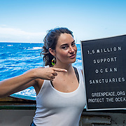"""Actress and advocate Shailene Woodley holding a sign that reads """"1.5 Million Support Ocean Sanctuaries! Greenpeace.org/protecttheoceans""""."""