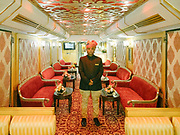 A waiter waits for guests on the Palace on Wheels, a vintage luxury train crossing Rajahstan province.