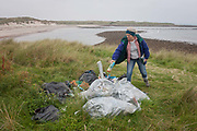 A woman throws a drinks bottle on to a pile of assorted plastic materials awaiting removal from the coastal landscape, having been collected by volunteers from a beach on Holy Island, on 27th September 2017, on Lindisfarne Island, Northumberland, England. The amount of rubbish found dumped on UK beaches rose by a third last year, according to a new report. More than 8,000 plastic bottles were collected by the Marine Conservation Society's annual beach clean-up at seaside locations from Orkney to the Channel Islands on one weekend in September 2016. The Holy Island of Lindisfarne, also known simply as Holy Island, is an island off the northeast coast of England. Holy Island has a recorded history from the 6th century AD; it was an important centre of Celtic and Anglo-saxon Christianity. After the Viking invasions and the Norman conquest of England, a priory was reestablished.