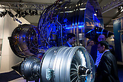 Potential buyers discuss airliner engine business with Rolls-Royce employee at the Farnborough Air Show.