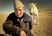 A Kazak horsemen, wearing a felt hat on his head, poses with his white horse in Mongolia.