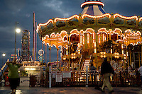Boardwalk carousel on Steel Pier in Atlantic City New Jersey, USA at twilight time; with Ferris Wheel in the background.