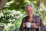 Portrait Of Mature Man In Garden With Coffee