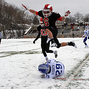 Myles Ridder, Darien, is tackled as Teddy Bossidy. New Canaan, jumps over him during the New Canaan Rams Vs Darien Blue Wave, CIAC Football Championship Class L Final at Boyle Stadium, Stamford. The New Canaan Rams won the match in snowy conditions 44-12. Stamford,  Connecticut, USA. 14th December 2013. Photo Tim Clayton