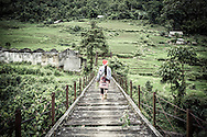 Red Dao woman crossing a bridge into Thanh Kim Commune, Sapa District, Lao Cai Province, Vietnam, Southeast Asia