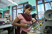 A Nepalese female factory worker sits at a sewing machine cutting material in the Surijha Traders garment factory in Kathmandu, Nepal.  The garments produced in the factory are exported around the world. The factory works closely with the Friends of Needy Children organization in providing fair employment opportunities for young Nepalese men and women.