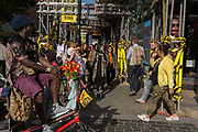 A rickshaw driver waits for customers on a busy street corner with yellow scaffolding protection sleeves and passing pedestrians on Long Acre near Covent Garden, on 1st September 2017, in London, England.