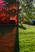 Red-tinted landscape against green grass caused by the Serpentine Gallery's Pavilion. Divided in half red and half green, late afternoon sunshine is backlit to reveal the shape and form of this building in one of London's most imminent of green spaces. The Serpentine's 40th Anniversary—the Serpentine Gallery Pavilion is designed by world-renowned French architect Jean Nouvel. The entire design is rendered in a vivid red that, in a play of opposites, contrasts with the green of its park setting. In London, the colour reflects the iconic British images of traditional telephone boxes, post boxes and London buses. The building consists of bold geometric forms, large retractable awnings and a sloped freestanding wall that stands 12m above the lawn. Striking glass, polycarbonate and fabric structures create a versatile system of interior and exterior spaces.