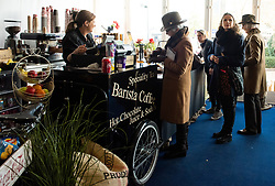 Raceoers buy hot drinks from the food stalls at Cheltenham Racecourse