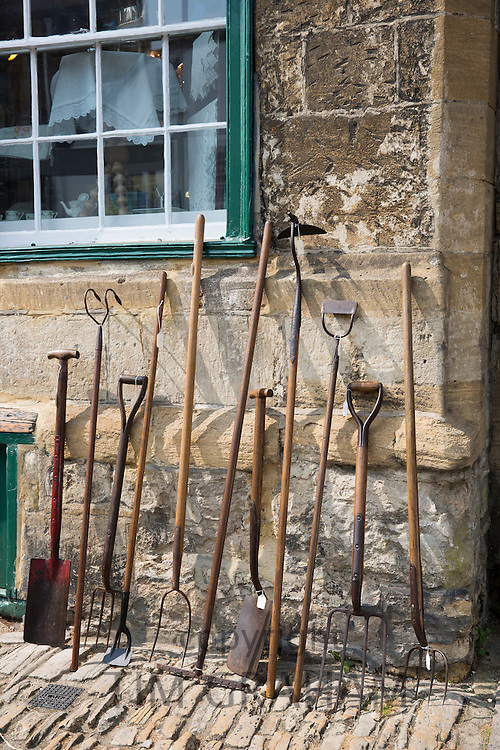 Old farming and gardening implements, garden tools at antique shop in Burford High Street , The Cotswolds, Oxfordshire, UK