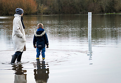 © Licensed to London News Pictures. 03/01/2021. Oxford, UK. A boy and his mother look at a monolith which has appeared in a flooded Oxford park. The object appeared overnight in Oatlands Park, West Oxford. It follows the appearance of similar monoliths in parts of the UK and around the world. Photo credit: Andre Camara/LNP