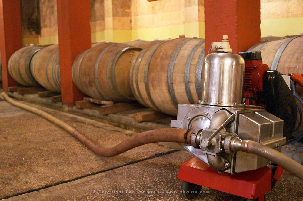 Barrels for storing the wine in wood. and a wine pump. Bodega Castillo Viejo Winery, Las Piedras, Canelones, Uruguay, South America