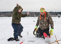 Bryson Chambers pulls in a good sized Pickerel with Joel Worden during Belknap County Sportmen's Club Kids Ice Fishing Derby on Lily Pond Sunday morning.  (Karen Bobotas/for the Laconia Daily Sun)