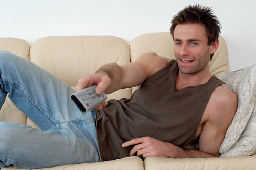 man laying on a sofa watching television changing channels with a TV remote, zapper<br />