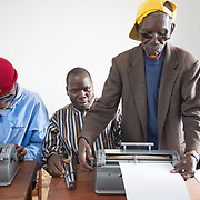 CAPTION: Braille class teacher Mr Bonomar sets up a typewriter for one of his students. The PWD community faces discrimination on a daily basis. Access to schools, jobs and public services is often limited. Responding to adult literacy challenges by teaching Braille helps ACAMO members to develop active voices for dialogue with the government. It also serves as a method of rehabilitation, building hope for participants that they will eventually be able to return to regular employment and be re-integrated into the mainstream workforce. LOCATION: Lulimile Village, Lichinga, Niassa Province, Mozambique. INDIVIDUAL(S) PHOTOGRAPHED: Casimiro Adua Caisse (left), Amido Bonomar (centre) and Fernando Joaninha (right).