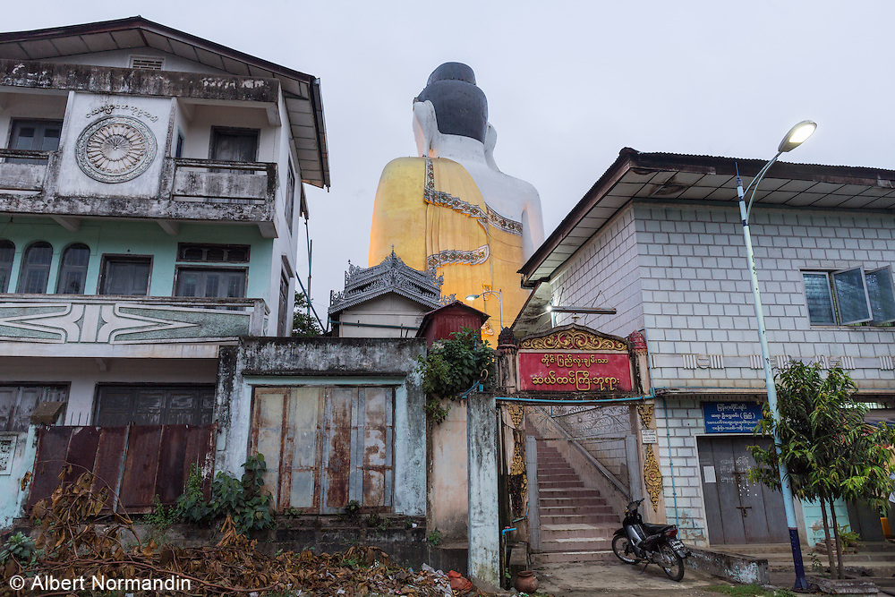 Back of sitting Buddha statue with old buildings of town, Pyay.