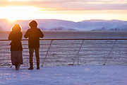Couple on deck looking at sun rising over scenic winter landscape, Havoysund, Norway