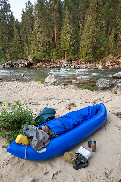 Sleeping in an inflatable kayak along the Selway River in Idaho.