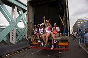Girls taking a rest on the back of a truck sound system on Sunday 28th August 2016 at the 50th Notting Hill Carnival in West London. A celebration of West Indian / Caribbean culture and Europes largest street party, festival and parade. Revellers come in their hundreds of thousands to have fun, dance, drink and let go in the brilliant atmosphere. It is led by members of the West Indian / Caribbean community, particularly the Trinidadian and Tobagonian British population, many of whom have lived in the area since the 1950s. The carnival has attracted up to 2 million people in the past and centres around a parade of floats, dancers and sound systems.