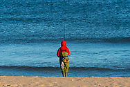 Spring Lake, NJ -- November 22, 2016. A winter fisherman waits patiently on the beach after casting his line.