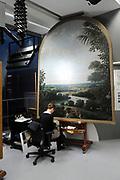 Staatsbezoek van de President van Slowakije , Zijne Excellentie president Ivan Gasparovic en zijn echtgenote Silvia Gasparovicova.<br /> <br /> Statevisit of the President of  Slowakije Ivan Gasparovic and his wife  Silvia Gasparovicova.<br /> <br /> Op de foto/ On the photo: <br /> <br />   Een Restaurator aan het werk in het restauratieafdeling van het Rijksmuseum met een schilderij van Frans Post , Landschap in Brazilie <br /> <br /> Restorers at work in the restoration department of the National Museum