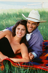 cowboy and a girl together on a blanket outdoors in a field