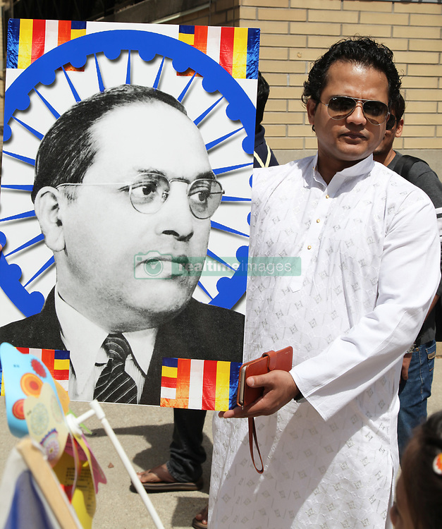 May 28, 2017 - Mississauga, Ontario, Canada - Indian Buddhist man holds a large poster of Dr. Bhimrao Ramji Ambedkar (Dr. Babasaheb Ambedkar) during the festival of Vesak in Mississauga, Ontario, Canada on 28 May 2017. Vesak (Wesak) commonly known as Lord Buddha's birthday celebration marks the birth, enlightenment and death of Lord Buddha. Dr. Ambedkar he founded the Bharatiya Bauddha Mahasabha, or the Buddhist Society of India in 1955 and later converted over 500,000 of his supporters to the Buddhist religion. (Credit Image: © Creative Touch Imaging Ltd/NurPhoto via ZUMA Press)