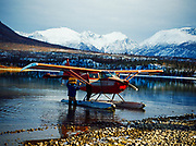 Former Governor Jay Hammond carrying box to Howard Bowman's Stinson Voyager 108 with PDX conversion, Hardenburg Bay of Lake Clark, Port Alsworth, Alaska.