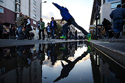 5 November 2017 - Premier League Football - Chelsea v Manchester United - A young fan jumps across a large puddle - Photo: Charlotte Wilson / Offside