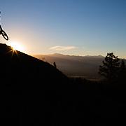 Malachi Artise gets air on his mountain bike at sunrise on Teton Pass near Wilson Wyoming. Parallel Trail.