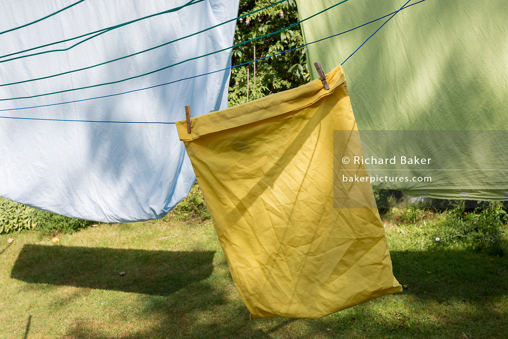 Green sheets and a yellow pillowcase dry on a washing line in a back garden of a south London residential house, on 18th August 2019, in London, England.